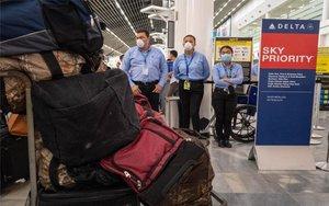 Personal de seguridad en un aeropuerto con mascarillas por el coronavirus.
