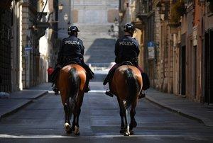 Dos policías a caballo patrullan por las calles vacías de Roma.