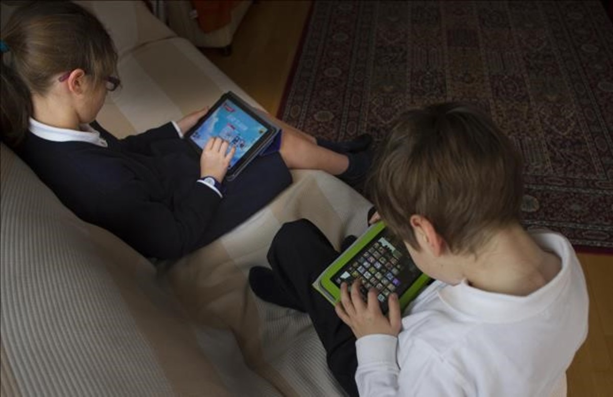Dos niños de 7 y 10 años juegan con una tablet.