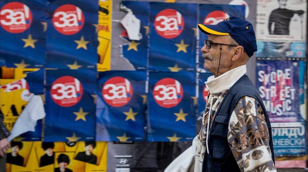 Un hombre camina junto a unos carteles a favor del 'sí' en el referéndum, en Skopje.