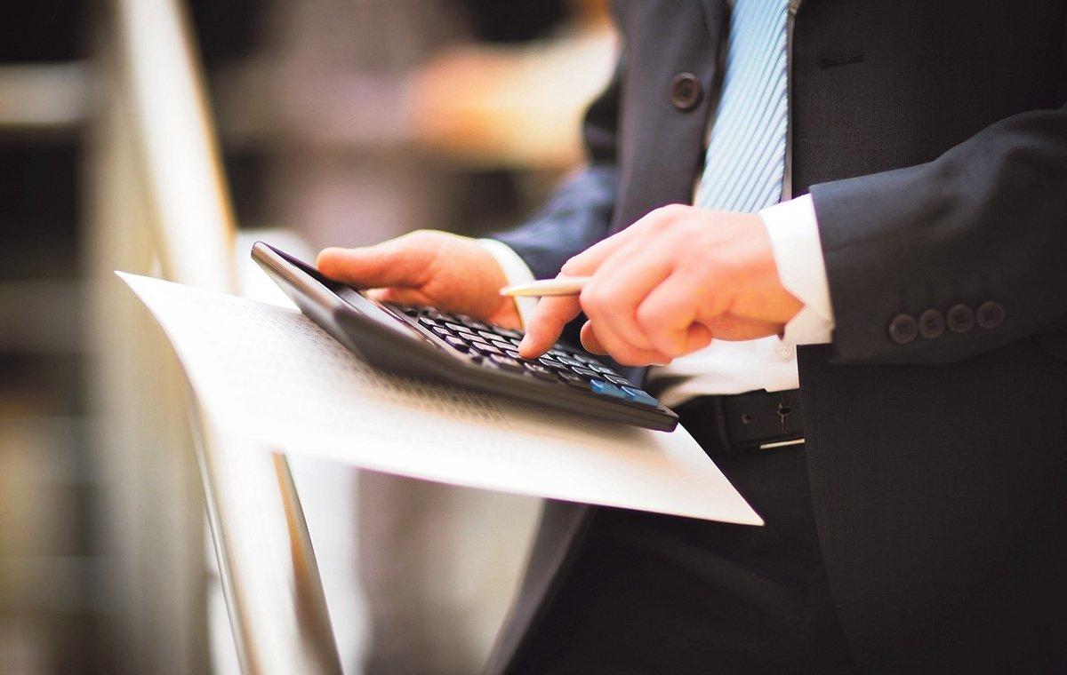 Un hombre hace números con la ayuda de una calculadora.