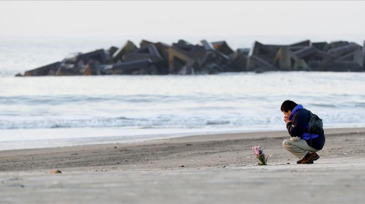 Un hombre realiza una ofrenda floral en la costa de Arahama, la zona donde impactó el tsunami el 2011.