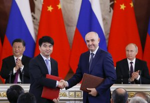 El vicepresidente de Huawei, Guo Ping,le da la mano al presidente ruso del operador de redes móviles MTS, Alexei Kornya; ante la presencia de Xi Jinping y Vladimir Putin.