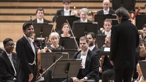 El violinista Julian Rachlin, a la izquierda, saluda altitular de la OBC Kazushi Ono, a la derecha deespaldas.