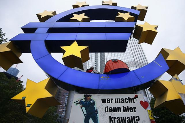Un manifestant planta la seva tenda al símbol de leuro durant el desallotjament del campament del moviment dels indignats davant de la seu del Banc Central Europeu (BCE), a Frankfurt (Alemanya).