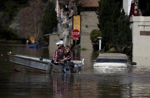 Pobladores intentan salir de una calle inundada en un poblado de California, EEUU. AFP
