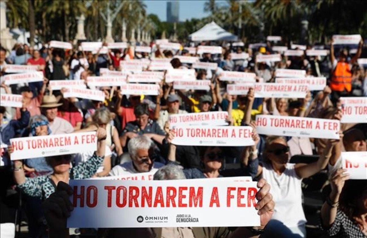Manifestación con carteles con el nuevo eslogan de Òmnium Cultural.
