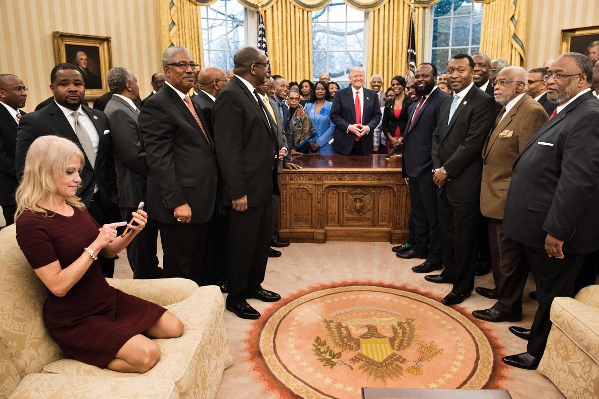 Kellyanne Conway, de rodillas sobre el sofá, consulta su móvil mientras Trump y sus invitados posan para la foto oficial.