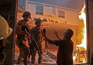 Un manifestante increpa a dos soldados en la sede en llamas de la Asociación de Bancos, en Beirut, este sábado.