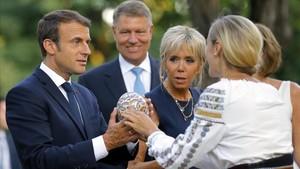 Macron (izq) y su mujer, Brigitte (centro), reciben un regalo junto al presidente rumano, Klaus Iohannis, en Bucarest, el 24 de agosto.