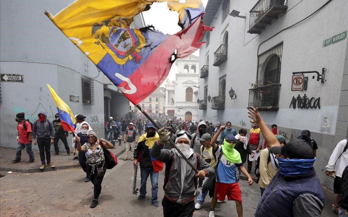 Manifestantes protestan contra el presidente Lenin Moreno y sus políticas económicas durante una marcha en Quito.