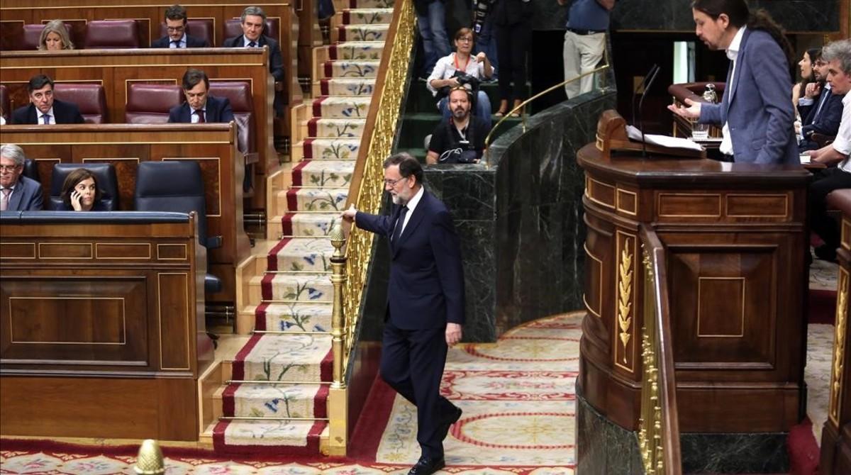 Mariano Rajoy vuelve a su escaño durante la intervención de Pablo Iglesias en la moción de censura.