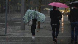 Paseantes bajo la lluviaen Barcelona, este martes.
