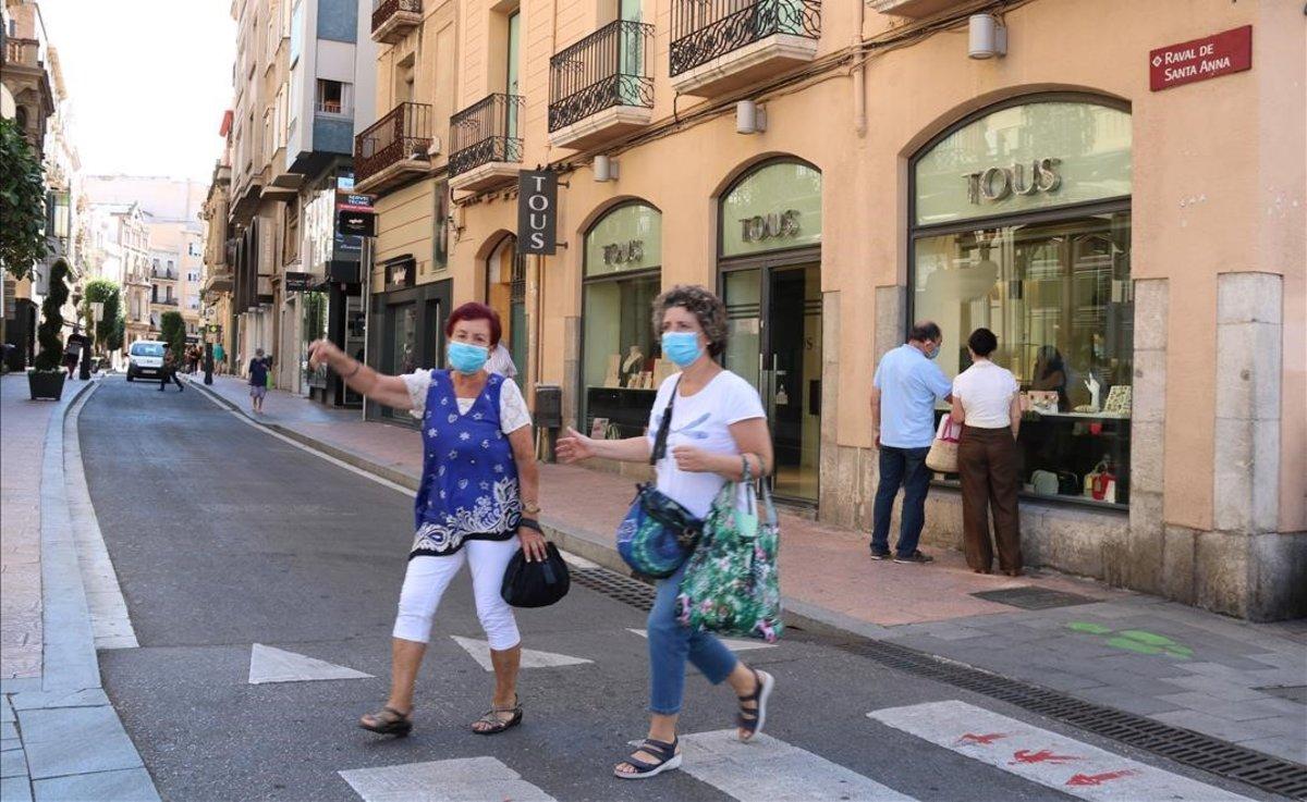 Peatones con mascarilla, en una calle de Reus.