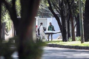 Peritos forenses se llevan a una de las víctimas del atentado en Ciudad de México.