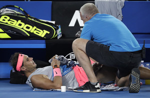 Spain's Rafael Nadal receives treatment from a trainer during his quarterfinal against Croatia's Marin Cilic at the Australian Open tennis championships in Melbourne, Australia, Tuesday, Jan. 23, 2018. (AP Photo/Dita Alangkara)