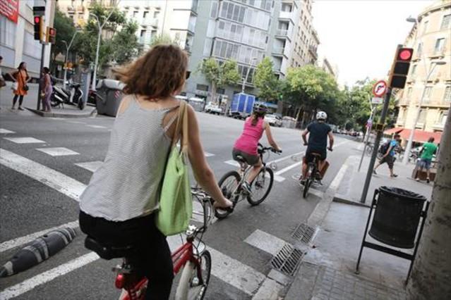 Ciclistas pasan un semáforo rojo en la calle de Consell de Cent, en Barcelona.