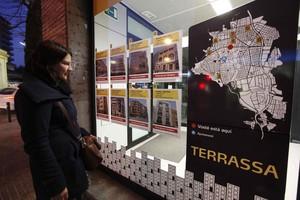 Una mujer mira precios de pisos en una inmobiliaria deTerrassa.