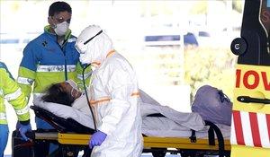 Una escena en la puerta del Hospital Puerta de Hierro de Madrid. El técnico de la ambulancia lleva un equipo de protección mínimo, en comparación con el del sanitario que recibe a la enferma.