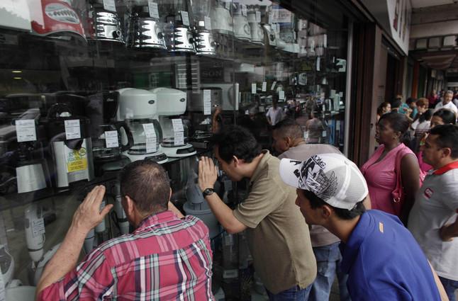 Venezolanos hacen cola ante una tienda de electrodomésticos, en Caracas.