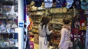 Turistas miran suvenires en una tienda en Las Ramblas