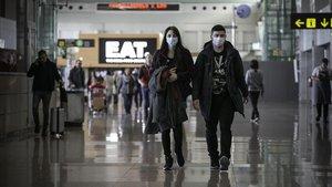 Pasajeros con mascarillas procedentes de Milán tras acceder al área de llegadas del aeropuerto de El Prat.