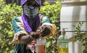 Una niña se protege la cara y se lava las manos en la ciudad de Uagadugú, en Burkina Faso.