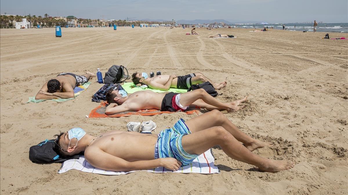 Bañistas con mascarilla, en la playa de la Malvarrosa, en València.