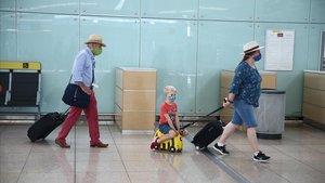 Sarah Butcher, su hijo y sus padres, se dirigen al aviónque los llevará a Londres tras facturar en una terminal semidesierta.