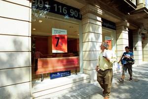 Dues persones passen davant duna oficina dING Direct a Barcelona.