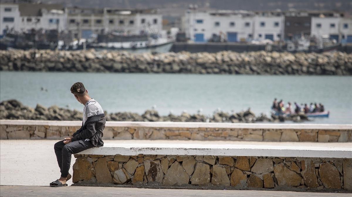 Un adolescente avista un barco que cruza el río que desemboca en el mar, en Larache.