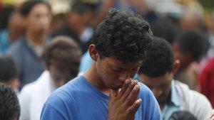 Un joven de la caravana reza en una ceremonia religiosaantes dellegar al puente fronterizode Tecun Uman, Guatemala, este domingo.