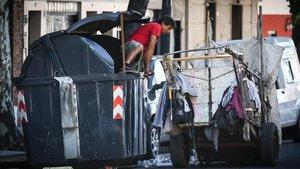 Un hombre busca en un viejo contenedor debasura en Buenos Aires.