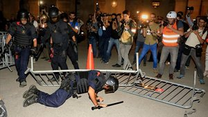 Un mosso acaba en el suelo tras tirarle una valla, en el Parlament.