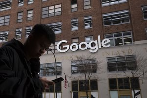 A man using a mobile phone walks past Google offices in New York  USA   AP Photo Mark Lennihan  FILE