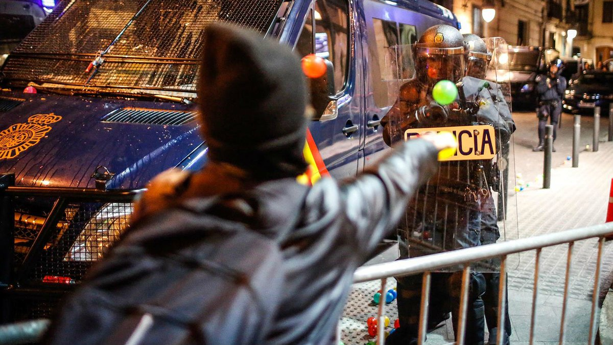 Un manifestante lanza una pelota a un policía, este sábado junto a la jefatura de Via Laietana