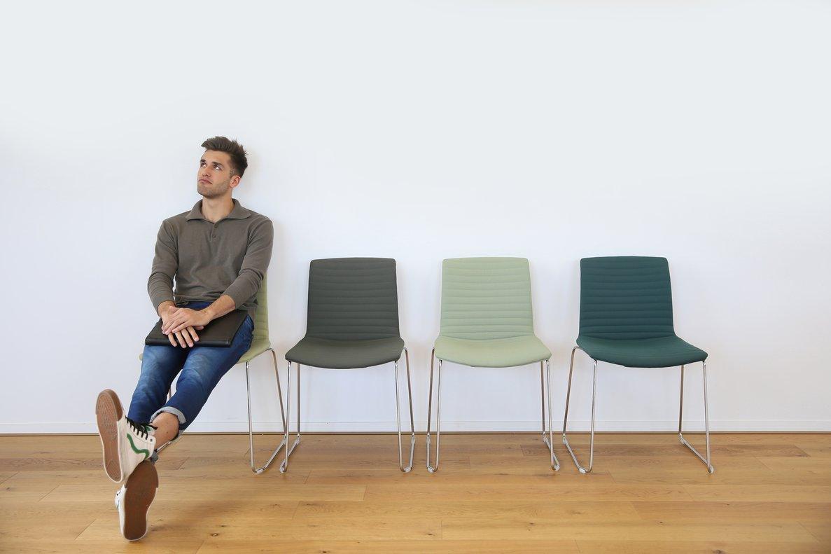 Un hombre sentado en una sala de espera.