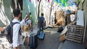 Un grupo de turistas cruza la calle de Tordera mientras los vecinos trabajan en la decoración.