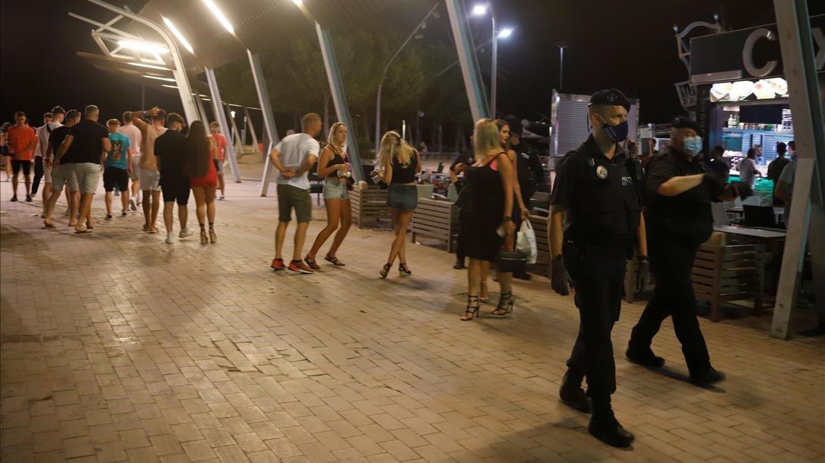 La Policía pasa delante de jóvenes sin msacarilla en Magaluf.