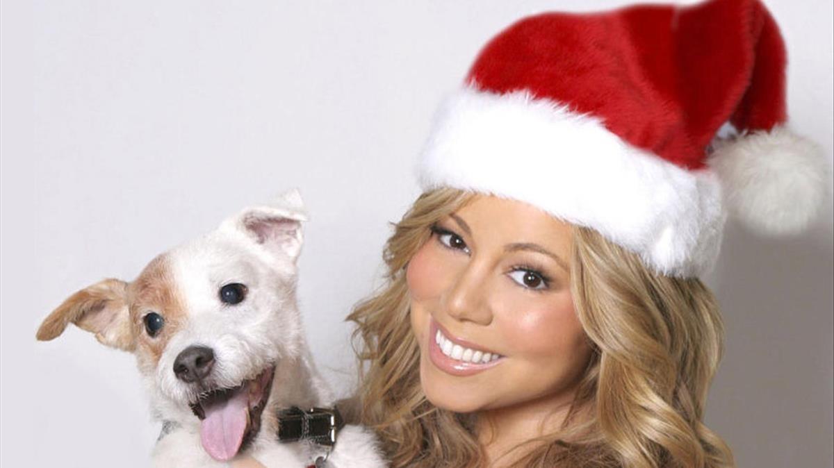 Una imagen de archivo de Mariah Carey, en una fotografía navideña, posando junto a un perro en el 2013.