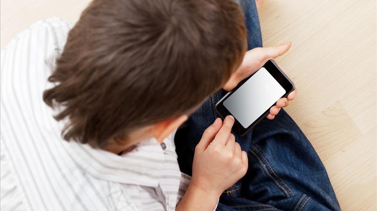 Un menor juega con un teléfono móvil.
