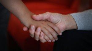 Un niño, cogidode la mano de un adulto, en Barcelona.