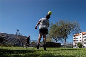 Un padre y un hijo juegan a fútbol en un parque de Palma, aprovechando las nuevas franjas de salida