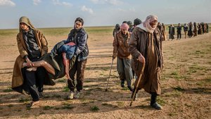 Presuntos militantes del Estado Islámico llevan en brazos a un herido, en la provincia siria de Deir Ezor