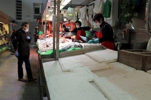 En primer término, una pescadería cerrada del Mercat del Lleó y, al fondo, pescaderías atendiendo a un cliente.