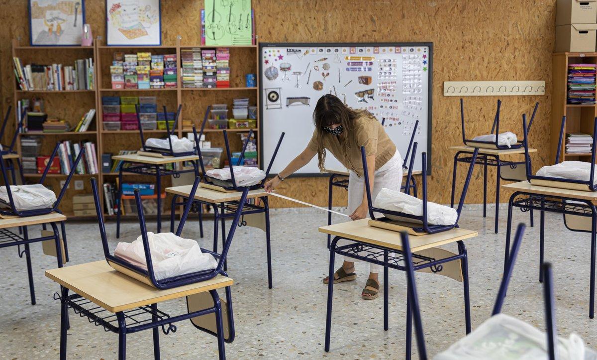 Una profesora mide la distancia de separación en un aula.
