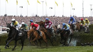Rule The World, montado por un jockey con chaquetilla roja, supera uno de los obstáculos en el espectacular Grand National.