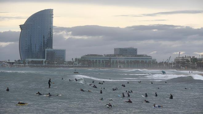 Surferos en la playa de la Barceloneta, en un día lluvioso.