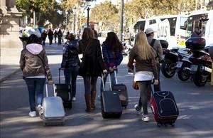 Turistas con maletas porlas calles deBarcelona.