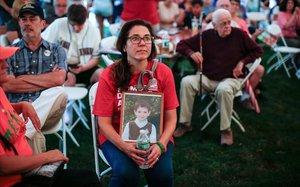 Una madre sostiene la foto de su hijo fallecido en la masacre.
